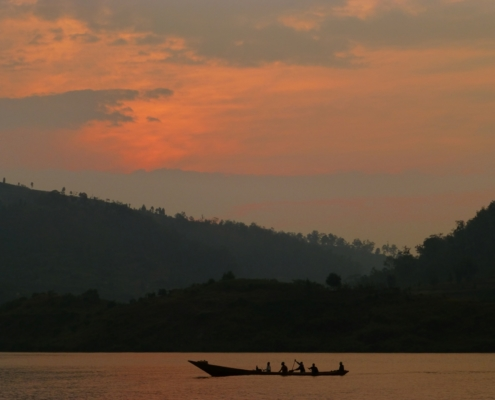 Fishermen row across Lake Kivu at sunrise off the peninsula of Kumbya, Rwanda